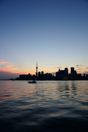 Toronto city skyline silhouette at sunset over lake with urban skyscrapers. Stock Photo - 20109642