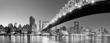 midtown manhattan: Queensboro Bridge over New York City East River black and white at night with river reflections and midtown Manhattan skyline illuminated.