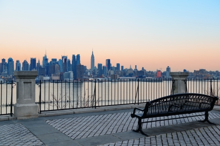 Bench in park and New York City midtown Manhattan at sunset with skyline panorama view over Hudson River Stock Photo