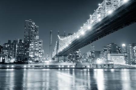 Queensboro Bridge over New York City East River black and white at night with river reflections and midtown Manhattan skyline illuminated. Stock Photo - 20368514