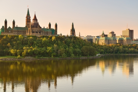 canada: Ottawa city skyline at sunrise in the morning over river with urban historical buildings and colorful cloud
