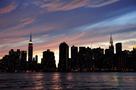 new: New York City Manhattan midtown silhouette panorama at sunset with skyscrapers and colorful sky over east river Stock Photo