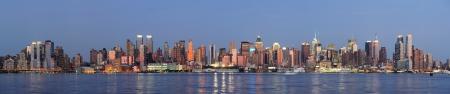 都市景観のパノラマと静かな青いトーンの光の反射と日没後ニューヨーク市マンハッタンのハドソン川ウォーター フロント ビュー。