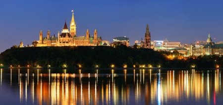 Ottawa at night over river with historical architecture. photo