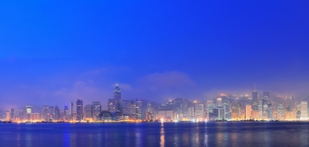 Hong Kong Victoria Harbor morning with urban skyscrapers over sea with blue tone and street light. photo