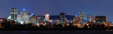 Montreal over river panorama at dusk with city lights and urban buildings photo