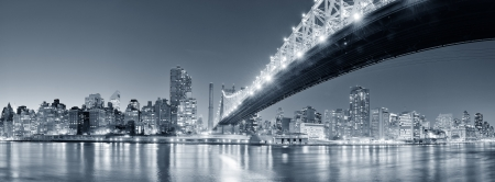 Queensboro Bridge over New York City East River black and white at night with river reflections and midtown Manhattan skyline illuminated. Stock Photo - 20601093