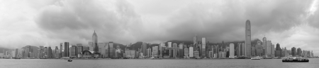 on the black sea: Urban architecture in Hong Kong Victoria Harbor with city skyline and cloud in the day in black and white.