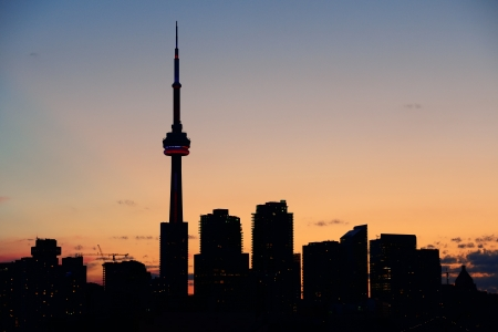 Toronto city skyline silhouette at sunset over lake with urban skyscrapers. Stock Photo - 20730396
