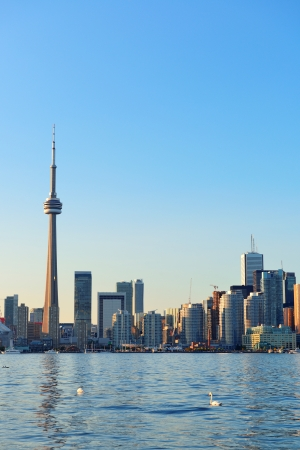 Toronto skyline in the day over lake with urban architecture and blue sky