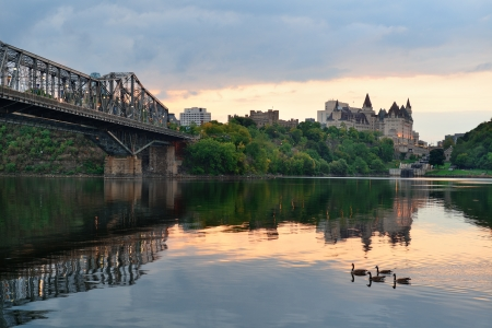 Ottawa city skyline at sunrise in the morning over river with urban historical buildings and colorful cloud