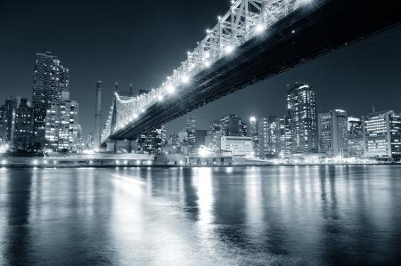 뉴욕시 이스트 강 Queensboro 다리 검은 색과 강 반사와 조명 미드 타운 맨해튼의 스카이 라인 밤에 흰색. 스톡 콘텐츠
