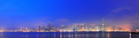 Hong Kong Victoria Harbor morning with urban skyscrapers over sea with blue tone and street light  photo