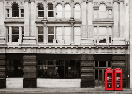 historical architecture: Red telephone booth in street with historical architecture in London.