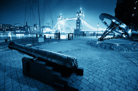 katherine: Cannon and Tower Bridge at night at St. Katherine Dock in London. Stock Photo