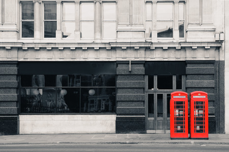 Red telephone booth in street with historical architecture in London. photo
