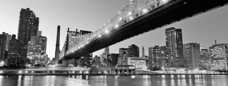 midtown: Queensboro Bridge over New York City East River black and white at night with river reflections and midtown Manhattan skyline illuminated.