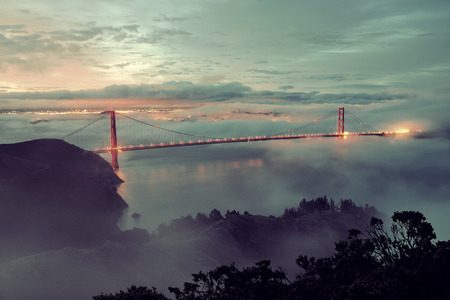 golden: Golden Gate Bridge and fog in San Francisco in early morning Stock Photo