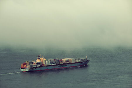 sf: San Francisco, CA - MAY 11: Cargo ship pass by San Francisco bay in fog on May 11, 2014 in San Francisco. SF is the most densely settled large city in California and the second-most in US. Editorial