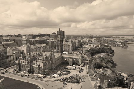 Ottawa cityscape in the day over river with historical architecture black and white. photo