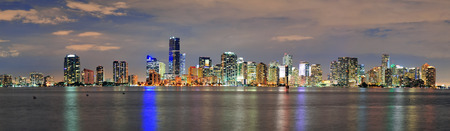 Miami city skyline panorama at dusk with urban skyscrapers over sea with reflection photo
