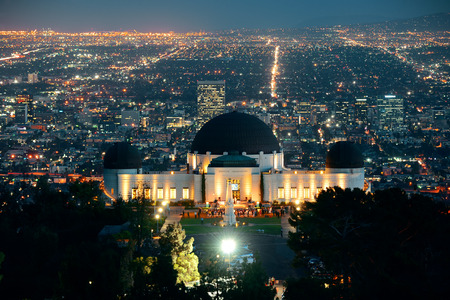 Los Angeles at night with urban buildings and Griffith Observatory photo