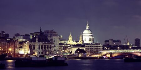 thames: London skyline at night with bridge and St Pauls Cathedral over Thames River. Stock Photo