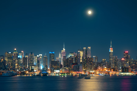 Moon rise over midtown Manhattan with city skyline at night photo