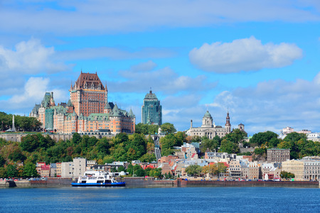 Quebec City skyline over river with blue sky and cloud.
