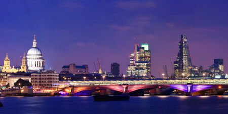 London skyline at night with bridge and St Pauls Cathedral over Thames River. Stock Photo