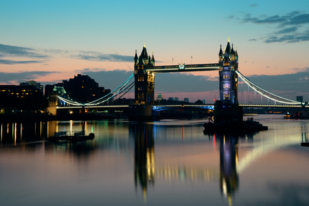 Tower Bridge with reflections in the morning over Thames River in London.