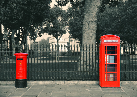 telephone box: Red telephone and post box in street with historical architecture in London.