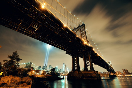 11: New York City downtown and september 11 tribute at night with Manhattan Bridge Stock Photo