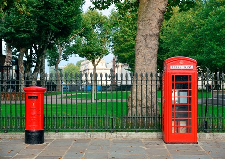 historical architecture: Red telephone and post box in street with historical architecture in London.