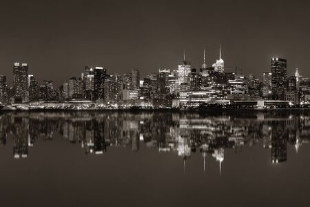 black: Midtown Manhattan skyline at dusk panorama over Hudson River with reflections