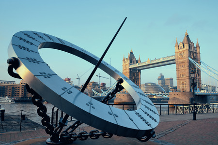 Tower Bridge and sundial over Thames River in London. Editorial