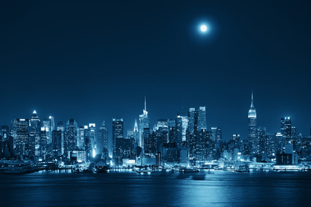 cities: Moon rise over midtown Manhattan with city skyline at night Stock Photo