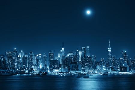 completo: Subida de la luna sobre el centro de Manhattan con el horizonte de la ciudad por la noche