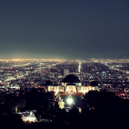 griffith: Los Angeles at night with urban buildings and Griffith Observatory Stock Photo