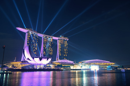 billion: SINGAPORE - APR 5: Marina Bay Sands hotel light show at night on April 5, 2014 in Singapore. It is the worlds most expensive building with cost of US$ 4.7 billion and landmark of Singapore.