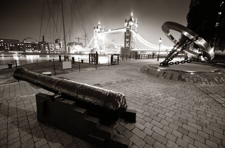 dock: Cannon and Tower Bridge at night at St. Katherine Dock in London. Stock Photo