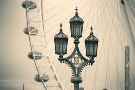 london eye: Vintage lamp post on Westminster Bridge in London in black and white.