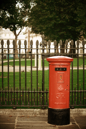 post box: Red post box in street with historical architecture in London.