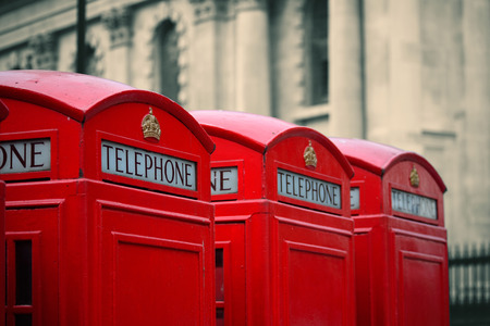 historical architecture: Red telephone box in street with historical architecture in London. Stock Photo