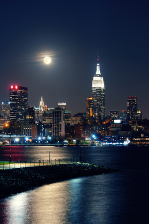 empire state: Moon rise over midtown Manhattan with city skyline at night Stock Photo
