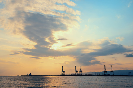 seaport: Osaka seaport with crane silhouette at sunset. Japan. Stock Photo