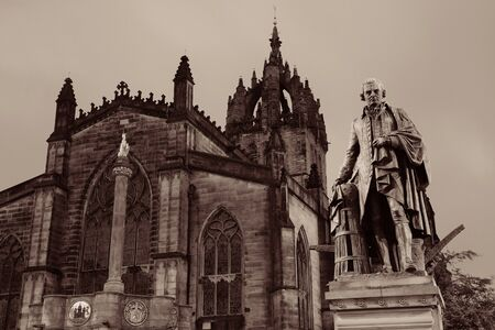 kirk: St Giles Cathedral with Duke of Buccleuch (Walter Scott) statue as the famous landmark of Edinburgh. United Kingdom.