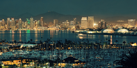 ports: San Diego downtown skyline at night with boat in harbor. Stock Photo