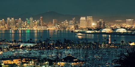 San Diego Skyline der Innenstadt in der Nacht mit Boot im Hafen.