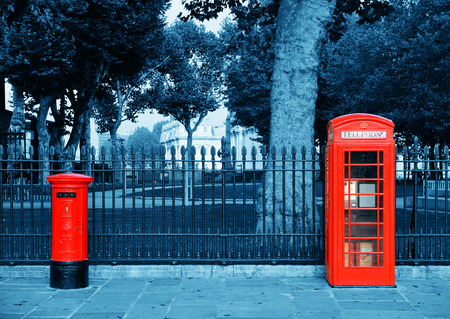 post box: Red telephone and post box in street with historical architecture in London.